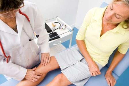врач осматривает колено пациентки