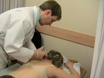 врач делает укол в шею