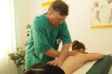врач разминает спину пациенту