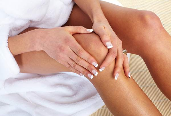 женщина держится руками за колено