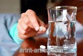 человек держит в руках таблетку, рядом стоит бокал с водой