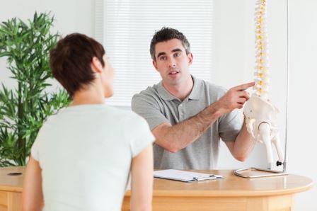 врач показывает женщине модель позвоночника