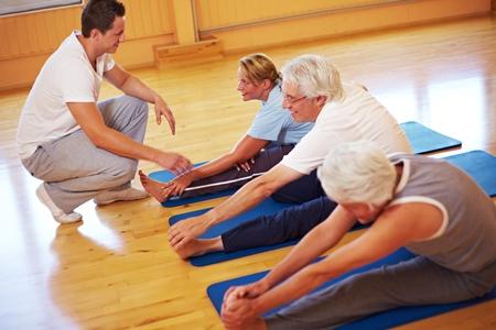 пожилые люди занимаются на ковриках