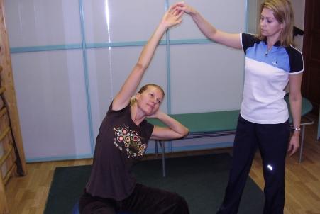 женщина сидит на фитболе с поднятой рукой