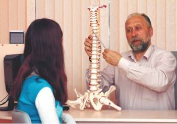 врач показывает макет позвоночника