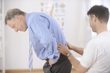 врач смотрит спину пациента