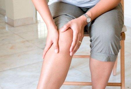 женщина трогает колено
