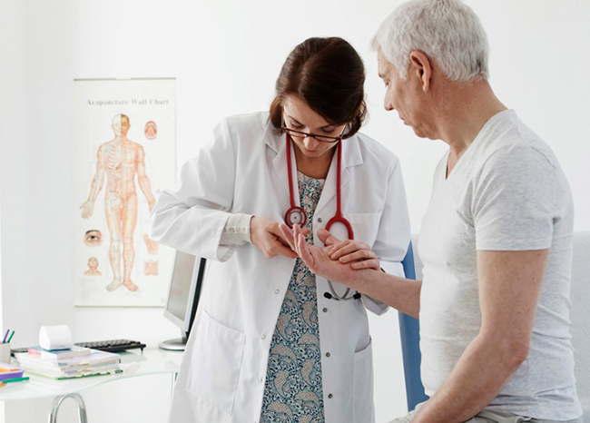 врач смотрит на руку пациента